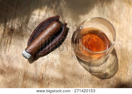 elevated view of close up cigar and drink on wooden table