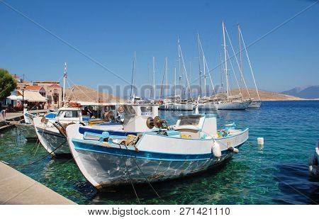 HALKI, GREECE - JULY 14, 2016: Small boats moored in Emborio harbour on the Greek island of Halki. The Dodecanese island is a popular destination for day trippers from Rhodes.