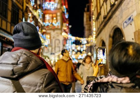 Rear View Of Couple Taking Photographs On Smartphone Telephone Mobile Devices Of The Garlands And De