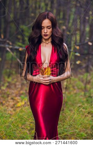 Woman In A Long Red Dress Alone In Forest. Fabulous And Mysterious Image Of A Girl In A Dark Forest