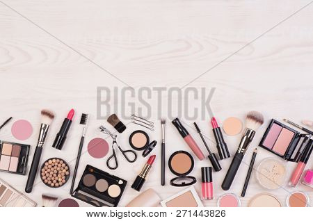 Makeup cosmetics such as eyeshadows, lipstick, mascara and makeup accessories on white, wooden background, top view with copy space