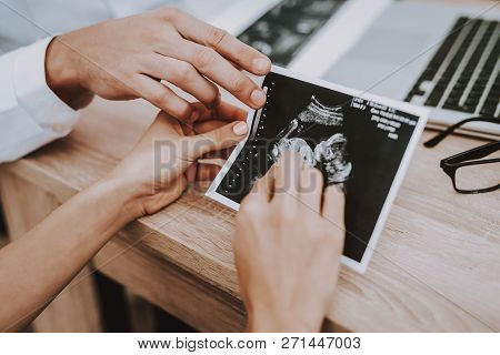 Pregnant Girl At The Gynecologist Male Doctor. Doctor Showing The Ultrasound Results To Woman. Peopl