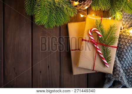 Cozy Winter Christmas Under Fir Tree Photo. Gifts Wrapped With Craft Paper, Decorated With Candy Can
