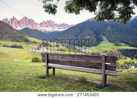 Bench With Alpine Village And Mountains On Background