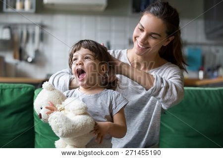 Smiling young mum making ponytail to little daughter poster