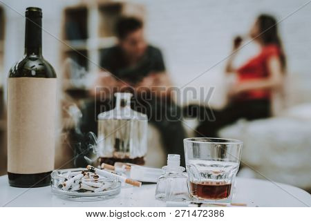 Cigarettes And Alcohol On Table. One Cigarette Is Burning. Alcohol Is Whiskey And Wine In Bottles. B