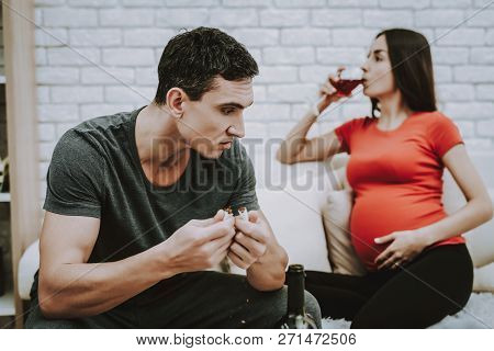 Man Is Shocked By His Wife. Wife Is A Young Pregnant Girl. Girl Is Drinking A Wine. Man Is Holding A
