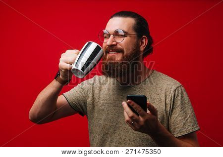 Happy Bearded Man Drinking Coffee Or Tea And Holding Phone