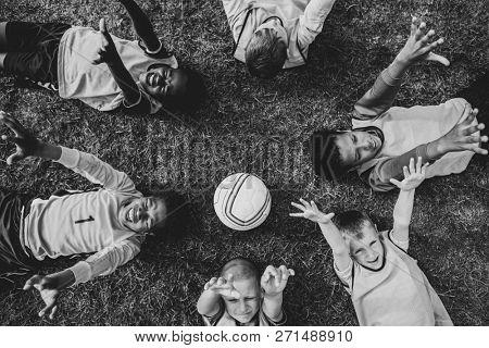 Junior football team lying around a football
