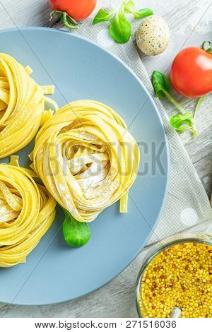 Raw Homemade Italian Typical Pasta Linguine Noodles On Plate, Quail Eggs, Green Lettuce, Tomatoes, F