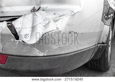 Silver Car With Rear Part Damaged In Crash Accident Or Collision With Scratched Paint And Dented Rea