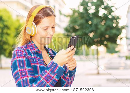 Smiling Woman Watch The Phone And Listen Music With Headphone