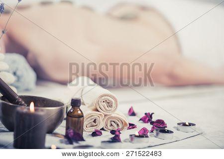 Beautiful Girl In Spa Salon. Adult Woman Having Hot Stone Massage In Spa Salon. Beauty Treatment Con