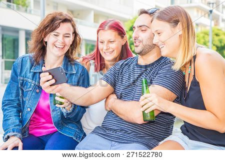 Group Of Friend Drinking A Beer And Whatching The Phone