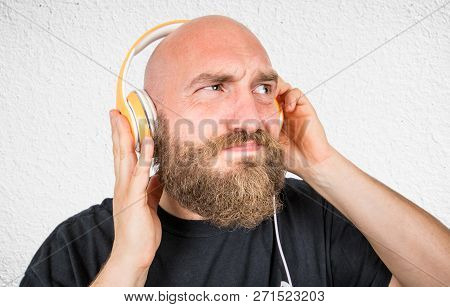 An Expressive Man Listen Music With Headphone