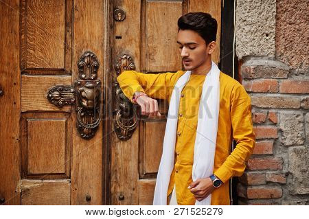 Indian Stylish Man In Yellow Traditional Clothes With White Scarf Posed Outdoor Against Old Gates.