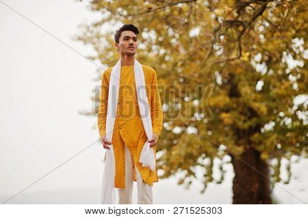 Indian Stylish Man In Yellow Traditional Clothes With White Scarf Posed Outdoor Against Autumn Leave