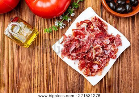 Appetizing Slices Of Iberian Ham On A Plate. On Wooden Background. It Includes Olive Oil, Fresh Toma