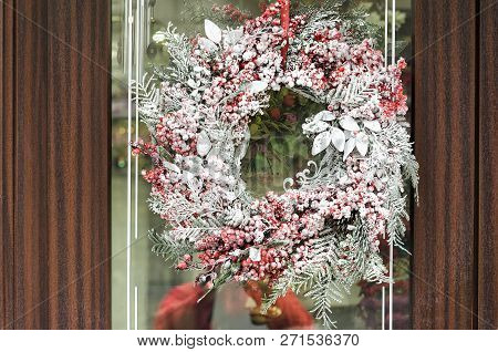 Christmas Wreath With With Red Snow-covered Berries Hanging On A Wooden Door.