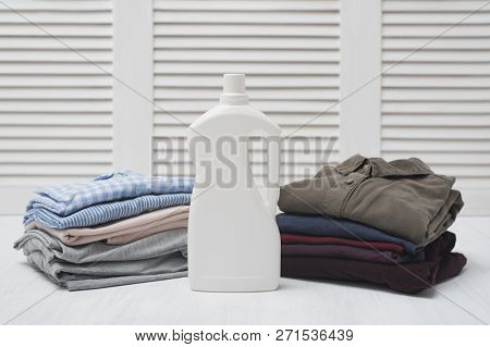 Two Stack Of Folded Clothes And Detergent Bottle. Dark And Light Linen