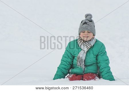 Boy In A Hat, Scarf And Green Jacket Sitting In The Snow. Portrait. Close-up. Winter Day