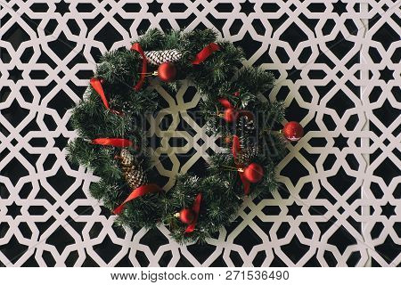 Christmas Wreath With Red Ribbons Hanging On The Wall With Carved Ornament.