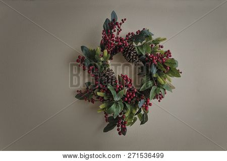 Christmas Wreath With Red Berries Hanging On A Light Gray Wall.
