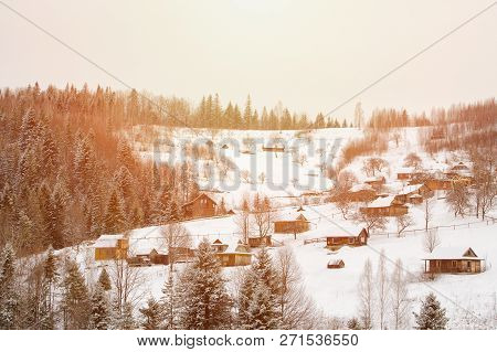 Snow-covered Hills, Forest And Houses In The Distance. Winter Landscape