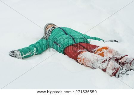 Boy In A Green Jacket And Red Pants Lying On His Back In Snow With Outstretched Arms. Winter Day