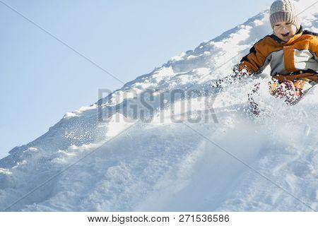 Boy In Hat And Orange Jumpsuit Slides Off Snow Slide On Back. Portrait. Winter Day