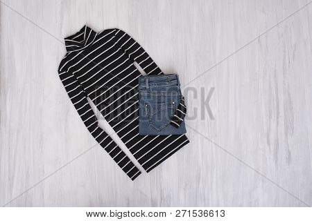 Black Striped Turtleneck And Jeans On Wooden Background. Fashionable Concept