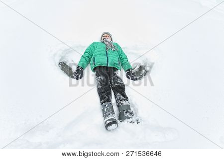 Boy In Hat, Scarf And Green Jacket Lying In Snow And Making Angel. Portrait. Close-up. Winter Day.