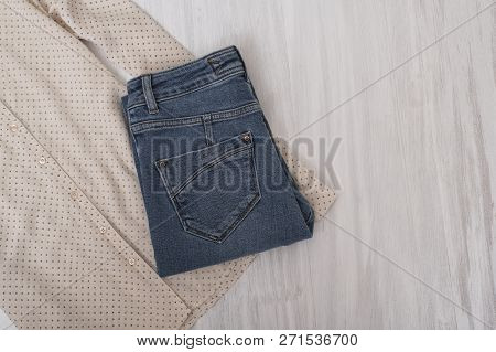 Fashionable Concept. Blue Jeans And A Part Of Beige Blouse On A Wooden Background. Female Wardrobe