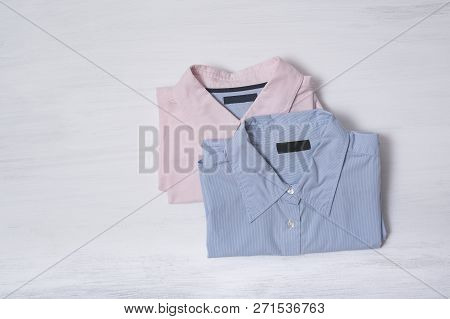 Two Folded Shirts On Wooden Background. Space For Text. Fashion Concept