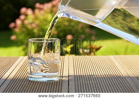 Pouring Clear Filtered Water From A Water Filtration Jug Into A Glass In Green Summer Garden In A Su