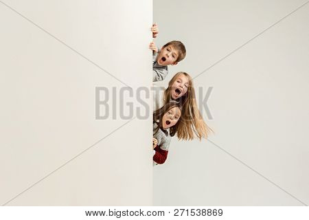 Banner With A Surprised Children Peeking At The Edge With Copyspace. The Portrait Of Cute Little Kid