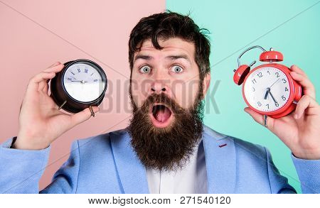Man Bearded Hipster Hold Two Different Clocks. Guy Unshaven Puzzled Face Having Problems With Changi