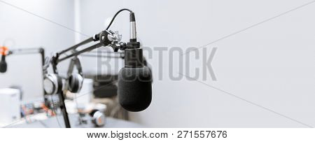 technology and audio equipment concept - microphone at recording studio or radio station