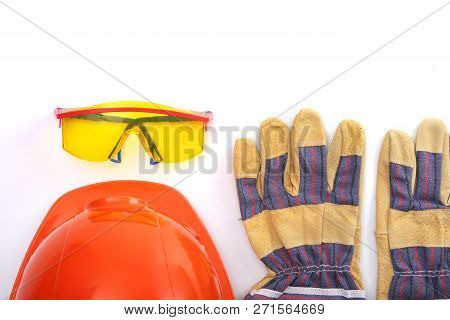 Orange Hard Hat, Leather Work Gloves And Safety Glasses On A White Background. Copy Space.