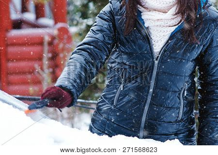 Man Cleaning Snow From Car Windshield With Brush, Close Up. Woman Removing Snow From Car. Snowy Wint