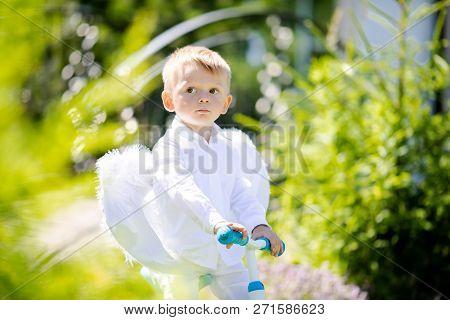 Toddler Boy Wearing Angel Wings Riding A Balance Bike (run Bike), Learning To Keep Balance On.. A Tr