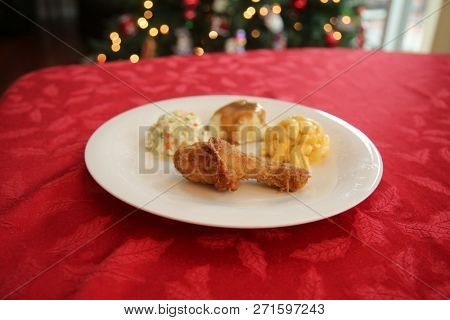 Chicken Dinner. Side View of a Chicken Dinner. White plate. Red Table Cloth. Chicken Leg. Biscuit. Coleslaw. Mashed Potatoes and Gravy. Macaroni and Cheese. A meal fit for a King. Christmas Tree.