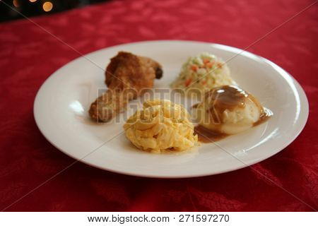 Chicken Dinner. Close Up View of a Chicken Dinner. White plate. Red Table Cloth. Chicken Leg. Biscuit. Coleslaw. Mashed Potatoes and Gravy. Macaroni and Cheese. A Meal fit for a King.