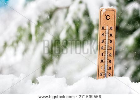 Thermometer showing freezing cold temperature in the snow concept for winter