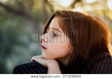 Profile Of A Young Girl With Her Chin Resting On Her Hand.  This Image Has A Vintage, Film Grain Loo