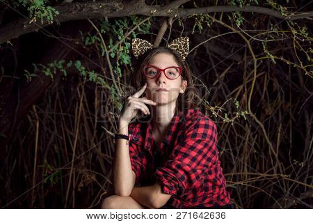A Teen Girl With Red Glasses And Leopard Ears Sits With A Contemplative Pose And Expression.  She Is