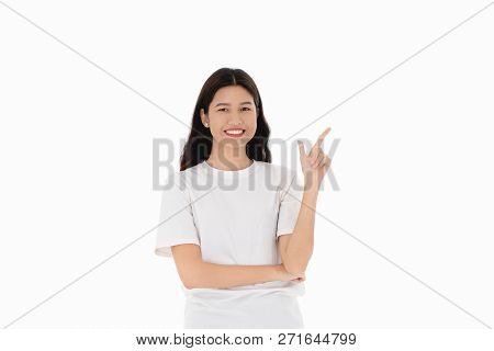 Portrait Of Young Asian Woman Pointing Her Finger In To The Air, Wears White T-shirt, Isolated In Wh