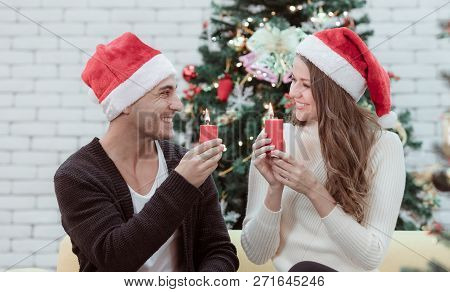 Young Caucasian Couple In Red Hat Sitting On Sofa Between Christmas Trees And Light Up Candles Toget