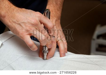 Hands Of A Chiropractor Use An Integrator On The Spine Of His Patient.  An Integrator Is An Instrume