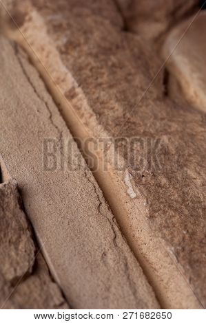 Stone Wall Of Natural Stones In Different Sizes. Rustic Stone Veneer In Shades Of Brown Color. Wall